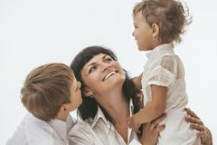 Woman smiling mother that kissing kids Stock Photo