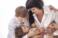 Woman smiling mother that kissing kids boy and girl Royalty Free Stock Image