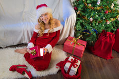 Woman smiling when opening christmas gift Stock Images