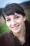 Woman smiling outdoors. Portrait of a young woman smiling outdoors Royalty Free Stock Photo