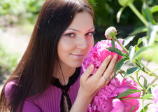 Woman smiling outdoors with some flowers Royalty Free Stock Photo