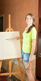 Woman smiling while painting a picture Stock Photo