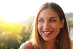 Woman smiling with perfect smile and white teeth thinking and looking sideways in park in summer. Sunlight flare. Copy space. stock images