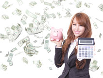 Woman smiling with piggy bank and calculator Royalty Free Stock Image