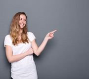 Woman smiling and pointing finger. Close up portrait of a young woman smiling and pointing finger to copy space on gray background Stock Photography