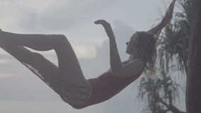 Woman smiling while relaxing on the hammock at the beach stock video
