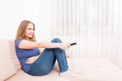 Woman smiling relaxing on sofa holding remote control Stock Image