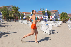 Woman smiling and running on beach near lounges Stock Photo