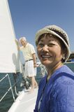 Woman smiling on sailboat husband in background (portrait) Royalty Free Stock Photos