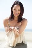 Woman smiling with sand falling through fingers Stock Photo