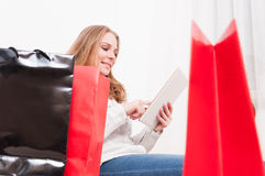 Woman smiling and shopping online with bags arround Stock Image