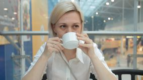 Woman smiling in the shot and drink a delicious cappuccino.  stock footage