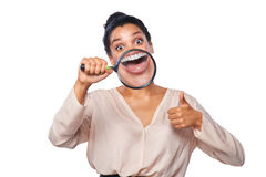 Woman smiling and show teeth through a magnifying glass Royalty Free Stock Image