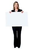 Woman smiling showing blank white placard Royalty Free Stock Photo