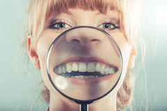 Woman smiling showing teeth with magnifying glass Royalty Free Stock Photos