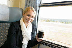 Woman smiling sitting in train holding coffee Royalty Free Stock Image