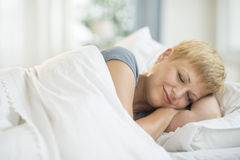 Woman Smiling While Sleeping In Bed Stock Photography
