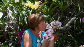 Woman smiling, smelling and admiring the colorful orchids stock video footage