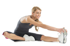 Woman Smiling While Stretching To Touch Her Toes Stock Photo