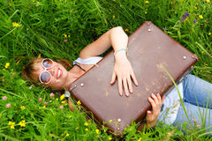 Woman smiling with suitcase in green grass Royalty Free Stock Photos