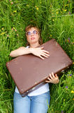 Woman smiling with suitcase in green grass Royalty Free Stock Image