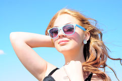 Woman smiling in the sun. Beautiful young woman with sunglasses smiling against blue sky Royalty Free Stock Photos