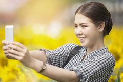 Woman smiling while taking selfie picture with mobile phone in s Stock Photo