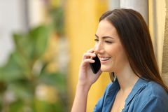Woman smiling talking on phone in the street stock photo