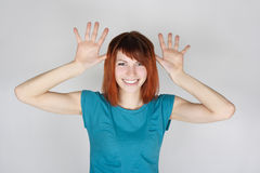 Woman smiling and teasing, opened palms near head Stock Photography