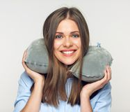 Woman smiling with teeth holding travel pillow on neck. Stock Image