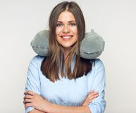 Woman smiling with teeth holding travel pillow on neck. Isolated advertising portrait Stock Photos
