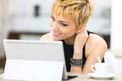 Woman smiling to a computer screen. Woman smiling at someone in her computer screen, she`s having a conference call or a romantic date, or she could talk with Royalty Free Stock Photo