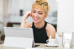 Woman smiling to a computer screen. Woman smiling at someone in her computer screen, she`s having a conference call or a romantic date, or she could talk with Stock Photography