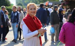 Woman smiling to the days of Bucharest celebration. Distributing leaflets with advertising royalty free stock photo