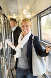 Woman smiling in train hall with luggage Stock Photos