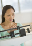 Woman Smiling While Using Balance Weight Scale Royalty Free Stock Photo