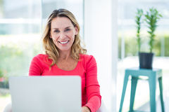 Woman smiling while using laptop Royalty Free Stock Photo