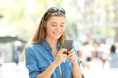 Woman smiling using a mobile phone in the street. Happy woman smiling using a mobile phone standing in the street Stock Image