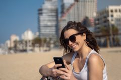 Young cute woman using smartphone on the beach. City Skyline In Background stock photos
