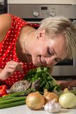 Cute girl smiling and watching over tortoise. Woman smiling and watching over tortoise. Vegetables on foreground Royalty Free Stock Photography