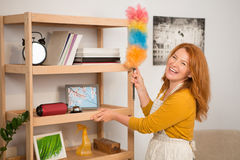 Woman smiling while wiping dust on wooden shelves. Time for cleaning red haired housewife doing routine work ay home Stock Images