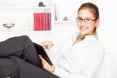 Woman smiling while working on tablet computer Royalty Free Stock Images
