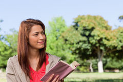 Woman smirking towards the side while reading a book Royalty Free Stock Photos
