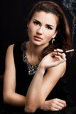 Woman smokes a cigarette. Beautiful woman smokes a cigarette Royalty Free Stock Photography