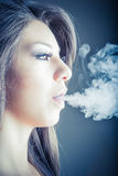Woman smokes in the dark Stock Photography