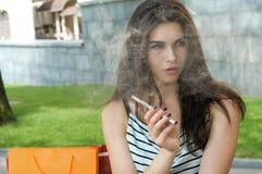 Woman smokes electronic cigarette. Stock Photography