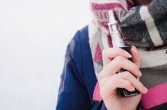 Woman smokes an electronic cigarette in the street near the snow-covered river Stock Photo