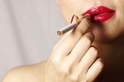Woman smokes in studio. Close up of cigarette in woman hand Royalty Free Stock Photography