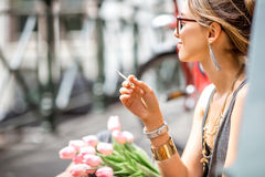 Woman smoking in Amsterdam city. Young beautiful woman smoking a cigarette sitting with flowers in Amsterdam city royalty free stock photo