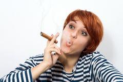 Woman smoking a cigar Stock Images